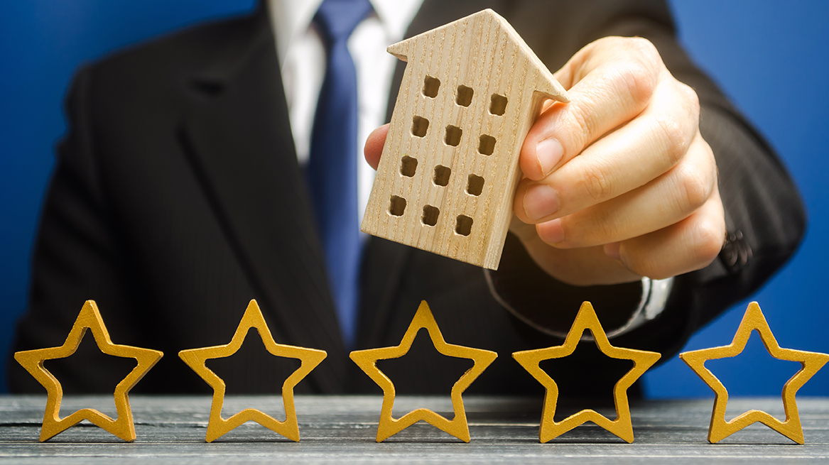 Extended-Stay-Jobs-Hotel-Star-Ratings-How-They-Work-man-holding-wooden-hotle-block-above-5-wooden-star-shapes